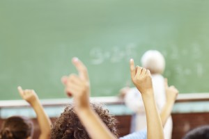 diverse hands raised classroom