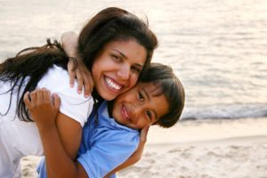Mother Hugging Son Tightly on the Beach