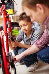 Portrait of little boy and his father repairing bicycle in garage