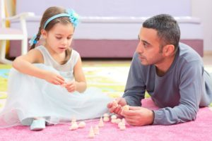 Father And Daughter Playing With Toys
